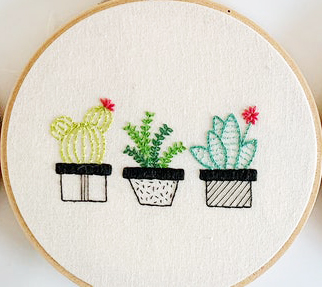 A trio of embroidered cactus on a embroidery hoop.