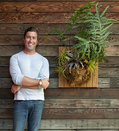 White guy wearing blue jeans and white shirt standing in front of wooden plank background with a planter on the wall