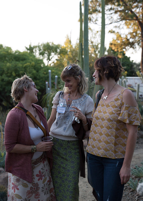 three white women laughing and enjoying time together in the garden