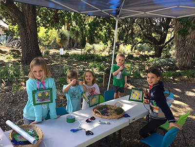 A group of children ages 5-10 enjoying a fun craft outdoors in the ruth bancroft garden junior cactus club