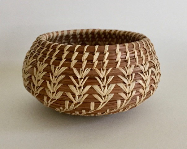 brown and tan basket weaved by hand from pine needles