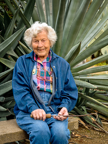 Smiling older woman in front of large agave plant