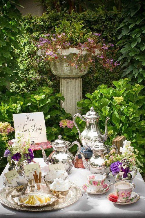 A table covered in fine silverware and tea pots stands in front of a lush green background of plants