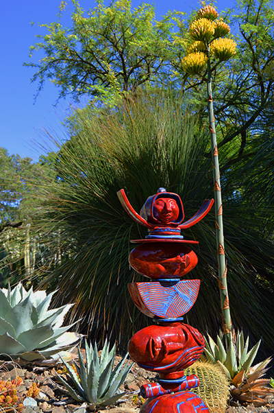 a red sculpture with heads and raised arms sits in front of blue agave plants, one of which is in bloom